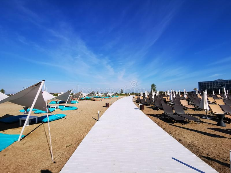 White wooden alley and sunbeds royalty free stock image