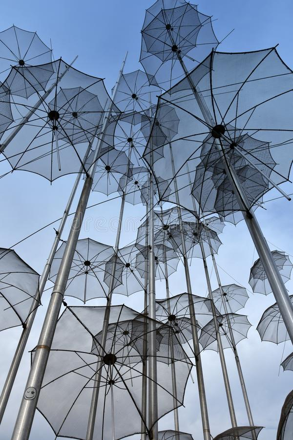 Umbrellas at the beach, sculpture of Giorgos Zongolopoulos. Umbrellas at the waterfront of Thessaloniki, Greece, under a blue sky. The artist is the greek royalty free stock photos