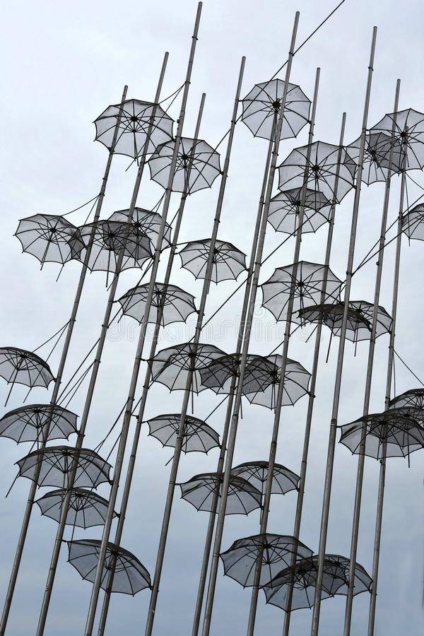 Umbrellas at the beach, sculpture of Giorgos Zongolopoulos. Umbrellas at the waterfront of Thessaloniki, Greece, under a cloudy sky. The artist is the greek royalty free stock image