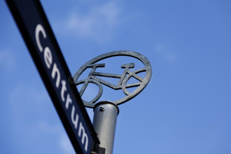 A sign with a bicycle icon that indicates that there is a bike path to the center of the city royalty free stock images
