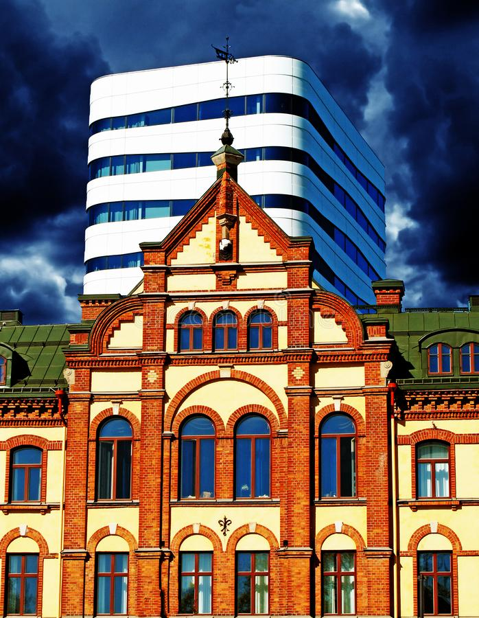 Umea, Swedmodern och gammalt hus i den samma bilden och storm i bakgrunden arkivbild