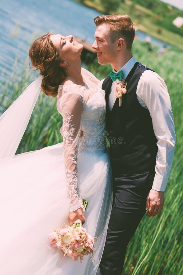 Umfassungslächelnde Braut des Bräutigams nahe blauem Teich lizenzfreie stockfotografie