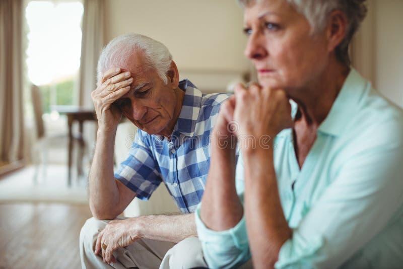 Umgekippte ältere Paare, die auf Sofa sich entspannen stockfotos