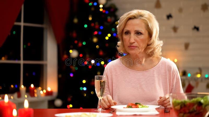 Umgekippte Dame, die nahe funkelndem Weihnachtsbaum, Einsamkeit im hohen Alter, Feiertag sitzt stockbilder