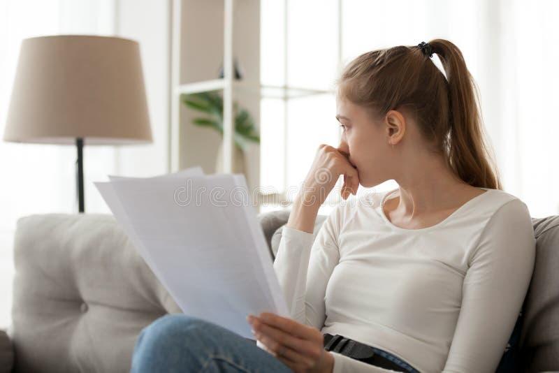 Umgekippte durchdachte Frau, die Papierdokument in den Händen, sitzend auf Sofa verwahrt stockfotografie