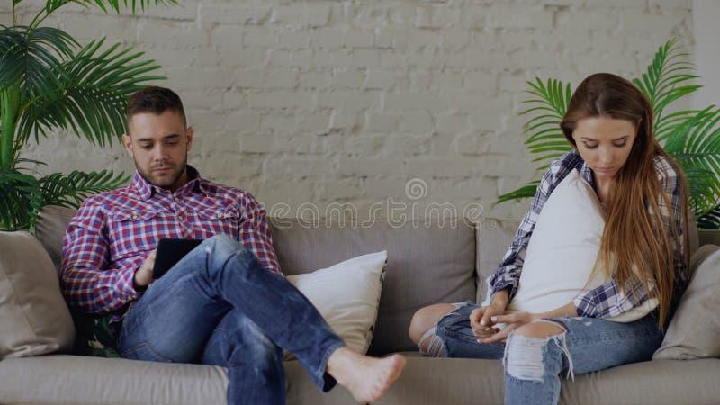 Umgekippte Frau der Junge ist betont und unglücklich, während ihr Freund, der Tablet-Computer verwendet, auf Couch zu Hause sitze lizenzfreies stockbild