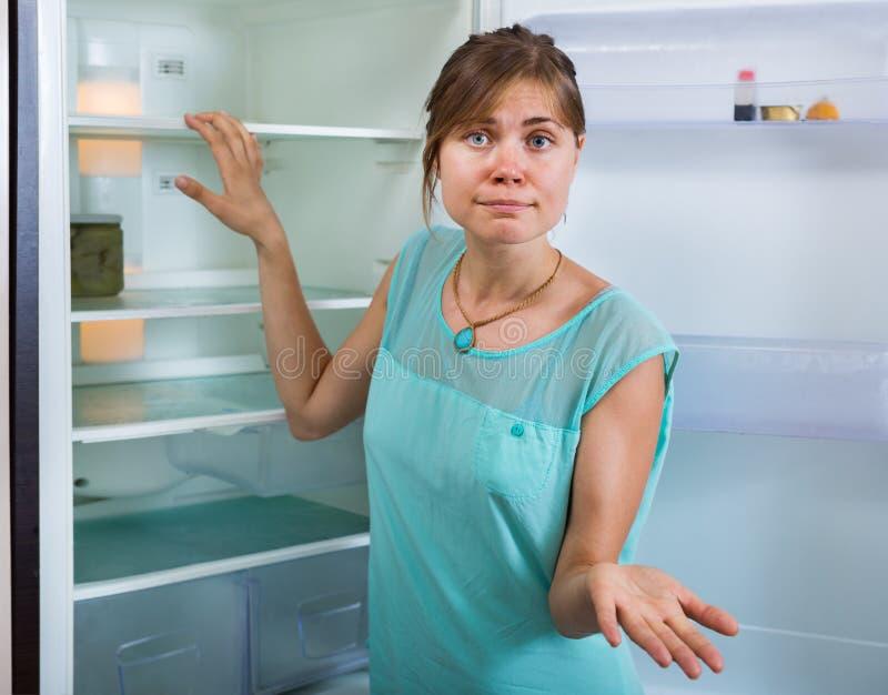 Umgekippte Frau, die leeren Kühlschrank betrachtet lizenzfreie stockfotografie
