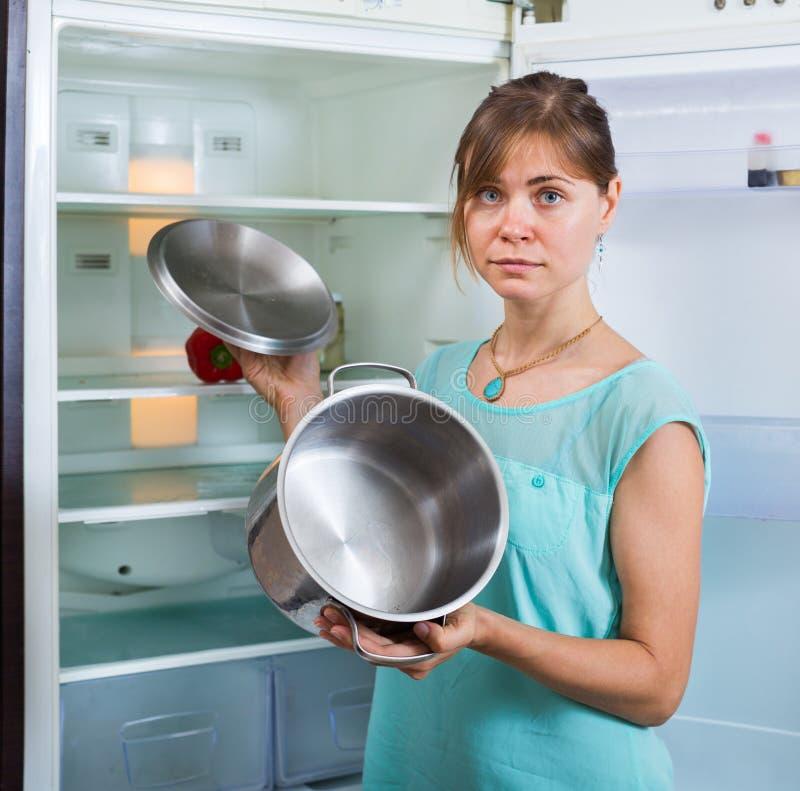 Umgekippte Frau, die leeren Kühlschrank betrachtet stockfoto