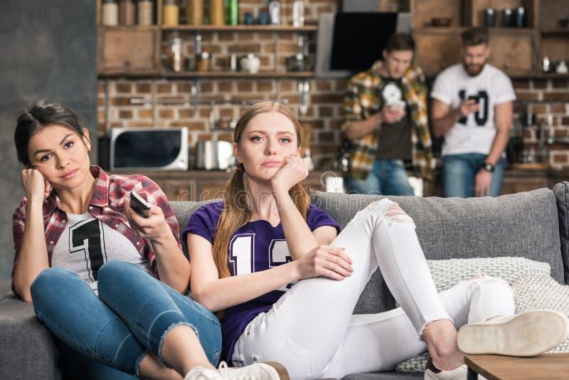 Umgekippte Frauen der Junge, die auf Sofa sitzen lizenzfreie stockfotografie