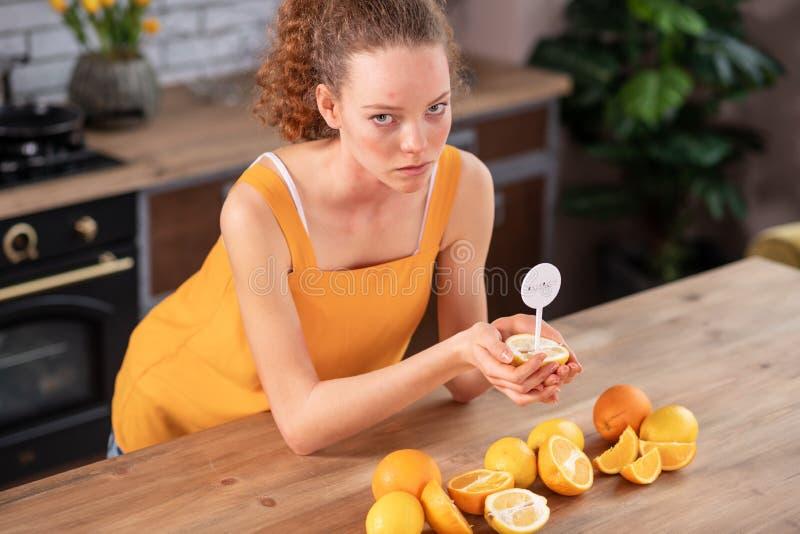 Umgekippte gelockte Frau, die helle gelbe Ausstattung trägt und auf Zitrone schaut stockfotografie