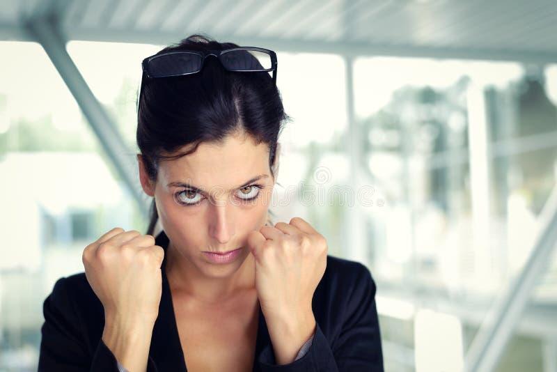 Umgekippte Geschäftsfrau bereit zu kämpfen stockfotografie