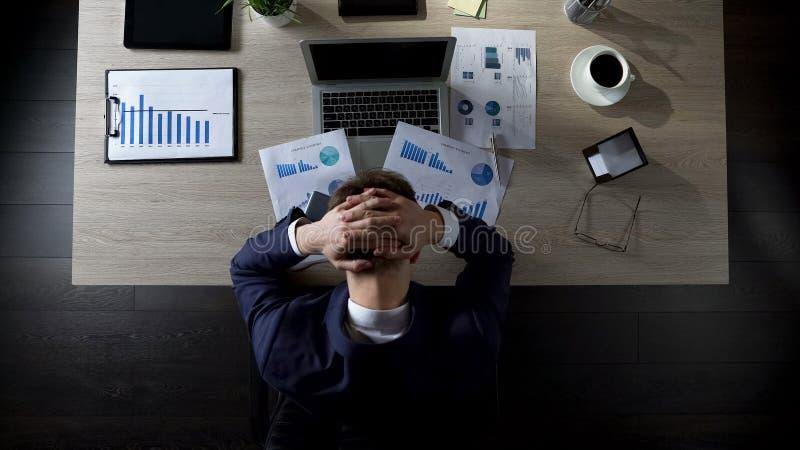 Umgekippte Geschäftsperson, die im Büro sitzt und an Schulden, Konkurs denkt lizenzfreie stockfotografie