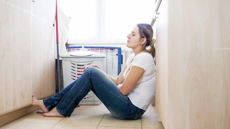 Umgekippte Hausfrau, die auf Waschmaschine an der Waschküche sich lehnt lizenzfreie stockfotos