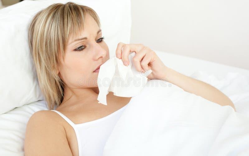 Umgekippte kranke Frau, die das Lügen auf ihrem Bett durchbrennt lizenzfreies stockbild
