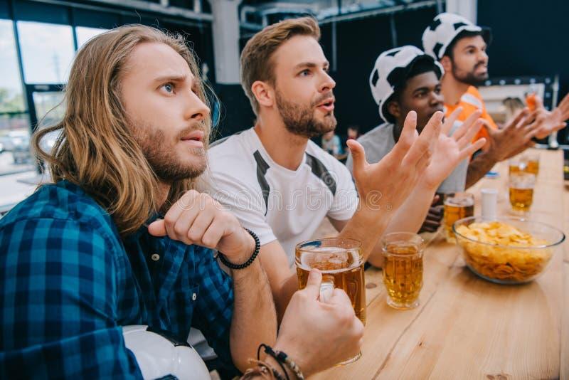 umgekippte multikulturelle Gruppe männliche Fußballfane in den Fußballhüten Bier trinkend und Fußballspiel aufpassend lizenzfreies stockbild