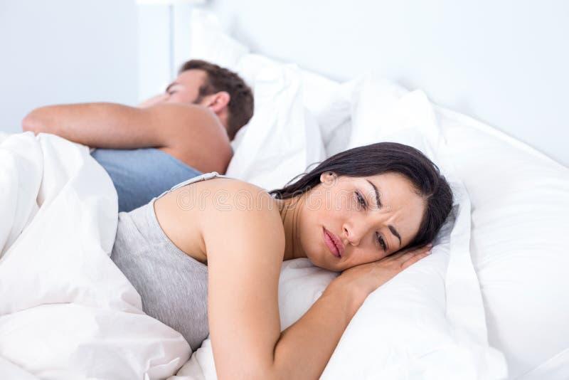 Umgekippte Paare, die auf Bett liegen stockfoto
