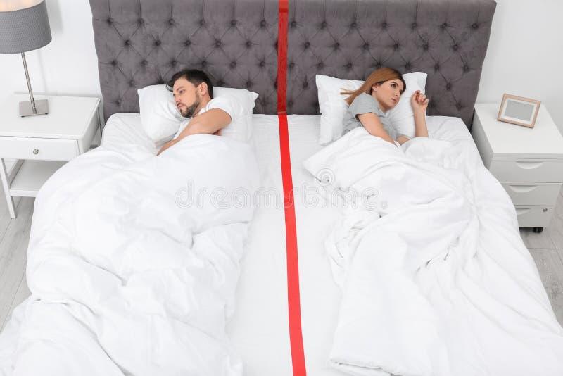 Umgekippte Paare mit den Verhältnis-Problemen, die separat liegen lizenzfreie stockfotografie