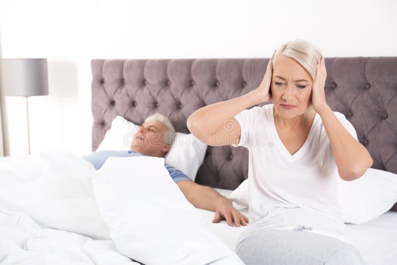 Umgekippte reife Frau, die zu Hause auf Bett nahe ihrem schlafenden Ehemann sitzt lizenzfreie stockfotografie