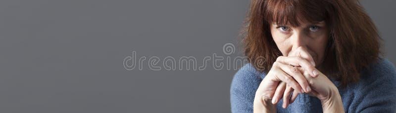 Umgekippte schöne schauende Frau 50s traurige, graue Kopienraumfahne stockfotos