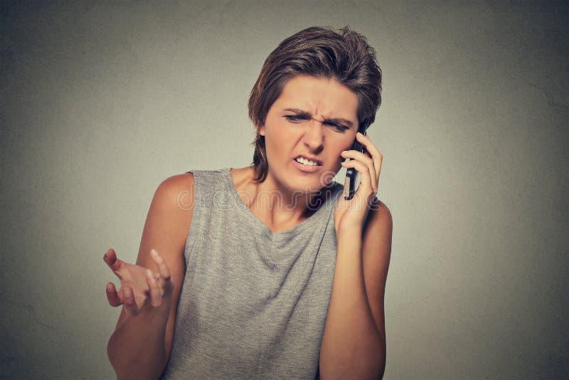 Umgekippte skeptische, unglückliche verärgerte Frau, die am Telefon spricht stockfotografie