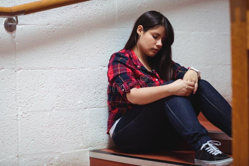 Umgekippte Studentin, die auf Treppenhaus sitzt stockbild