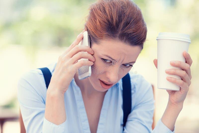 Umgekippte traurige, skeptische, unglückliche, ernste Frau, die am Telefon spricht stockfotos