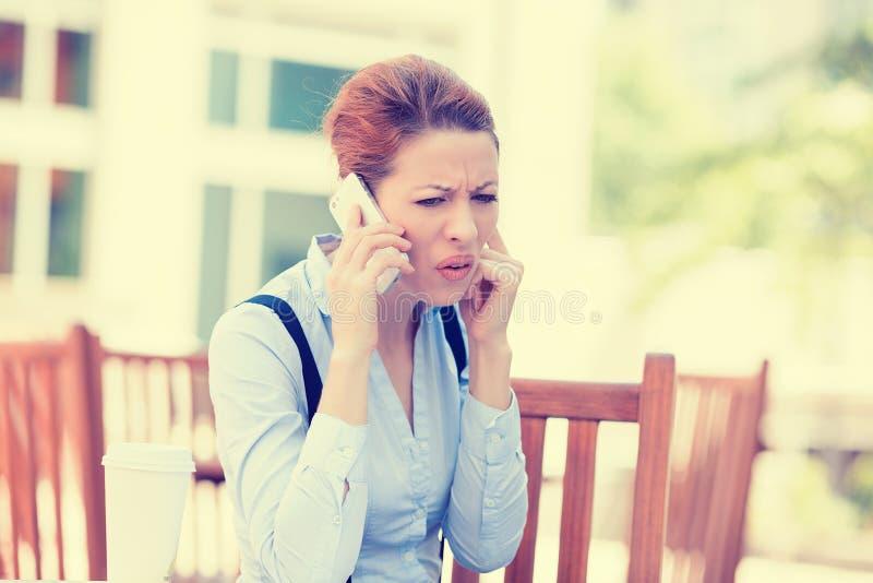 Umgekippte traurige skeptische unglückliche ernste Frau, die am Telefon spricht lizenzfreie stockbilder