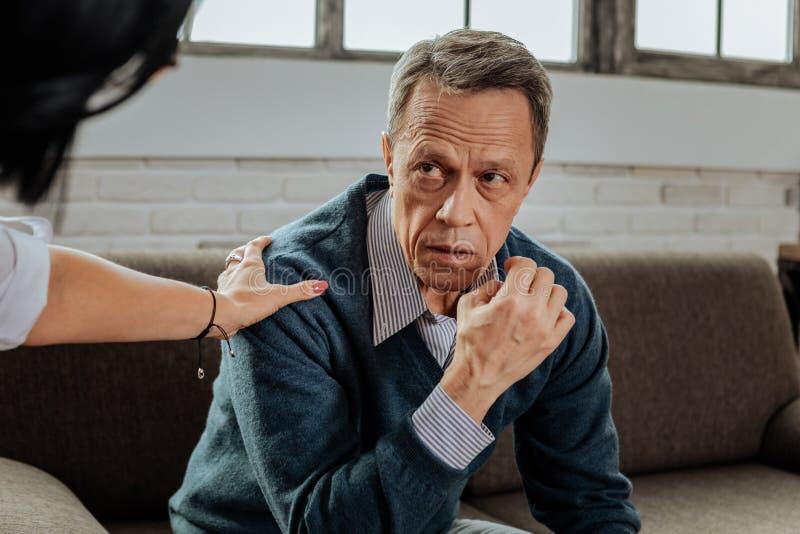 Umgekippter alter Mann im Hemd und in Strickjacke, die düster ist lizenzfreie stockbilder