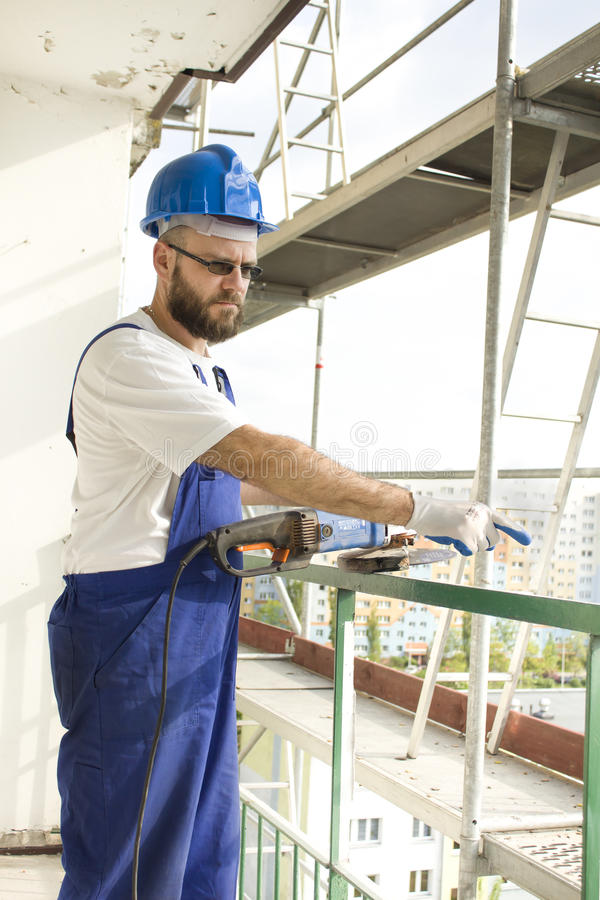 Umgekippter Bauarbeiter in einer Arbeitsausstattung und in einem Schutzhelm zeigt einen Finger Arbeit über hohes Baugerüst stockbild