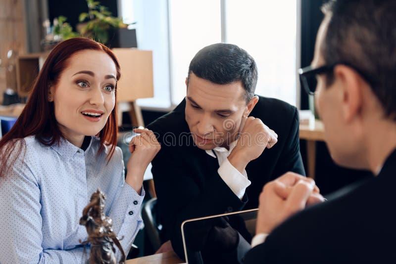 Umgekippter Ehemann sitzt mit junger Frau hinter Scheidungsanwalt ` s Tabelle stockbild