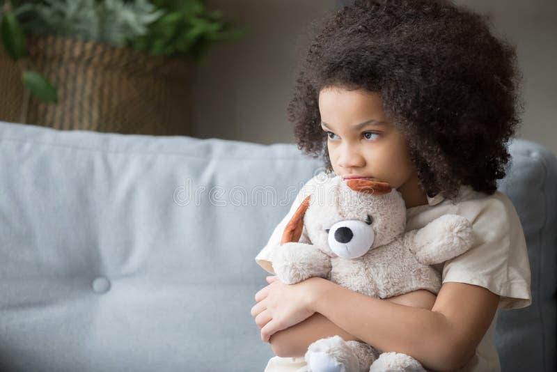 Umgekippter einsamer afrikanischer Kindermädchen-Holdingteddybär, der weg schaut lizenzfreie stockfotos