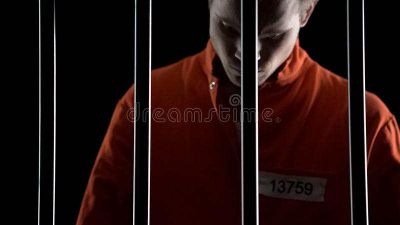 Umgekippter festgenommener Mann in der orange Klage hinter Gefängnisstangen, Todesstrafurteil stockbild