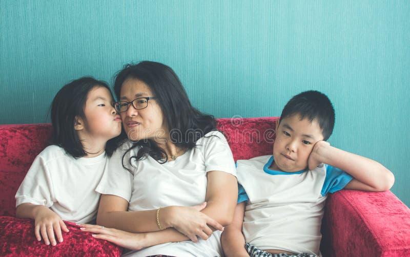 Umgekippter Junge, der auf der Sofamutter genießt mit Schwester auf Sofa an sitzt lizenzfreies stockfoto