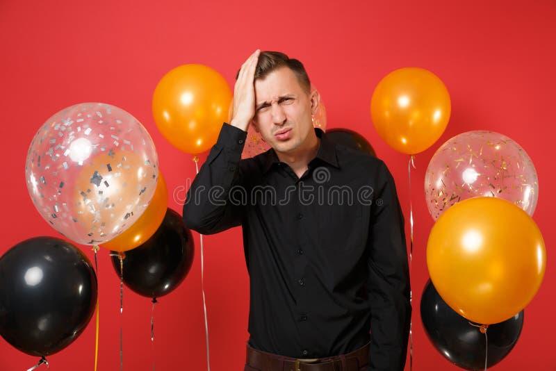 Umgekippter junger Mann im klassischen Hemd, das Hand auf Kopf, Kopfschmerzen auf roten Hintergrundluftballonen habend setzt St.- lizenzfreies stockbild