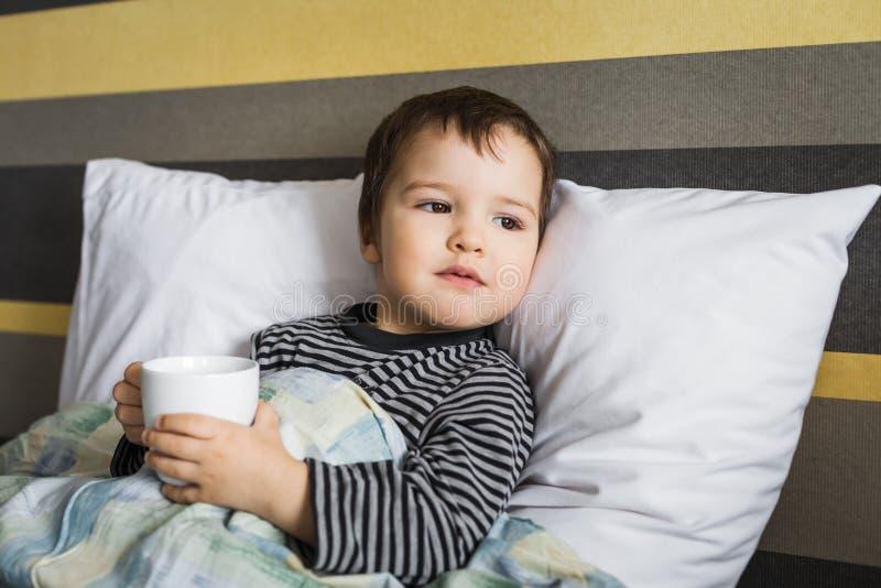 Umgekippter kurierender Junge des Kranken mit der Schale des Medikaments liegend auf Bett lizenzfreies stockfoto