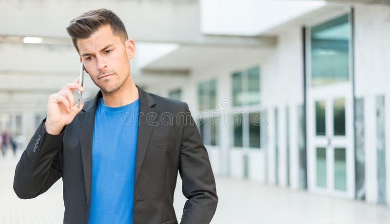 Umgekippter Mann, der am Handy spricht lizenzfreie stockfotografie