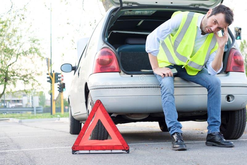 Umgekippter Mann, der nach unerwartetem Autozusammenbruch wartet lizenzfreie stockfotografie