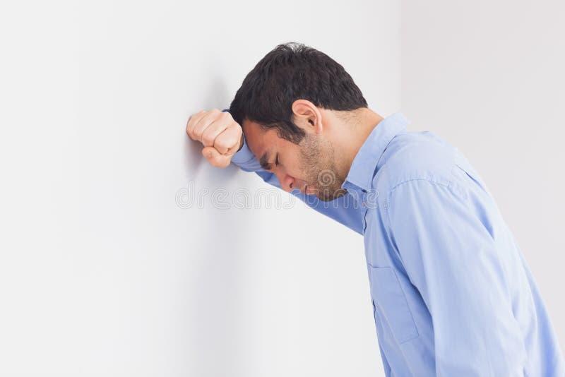 Umgekippter Mann, der seinen Kopf an einer Wand lehnt stockbilder