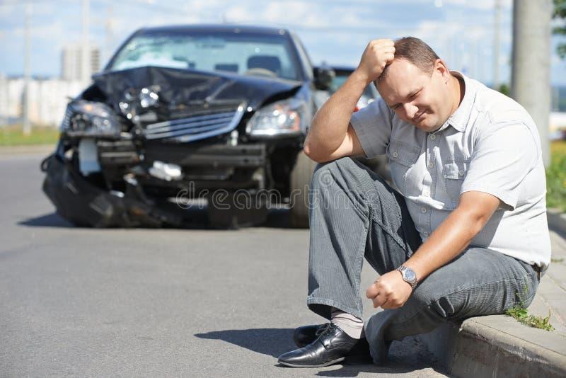 Umgekippter Mann nach Autounfall stockbilder