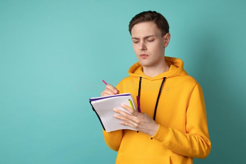 Umgekippter schöner Mannstudent in der zufälligen Kleidung, die gegen blaue Wand mit Notizbuch und Stift in den Händen steht stockfotografie