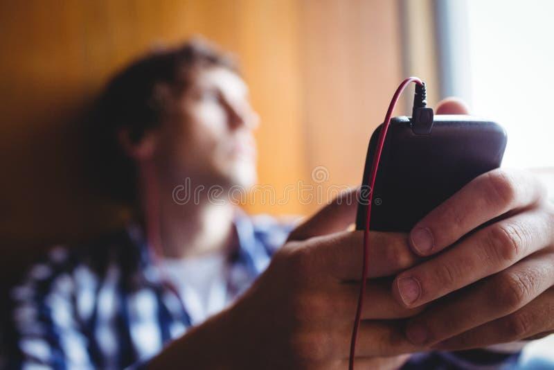 Umgekippter Student, der durch Fenster und hörende Musik schaut lizenzfreie stockbilder