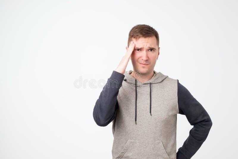 Umgekippter unglücklicher europäischer Mannstudent, der Kopf mit den Händen, krümmend in den Schmerz zusammendrückt und leiden un stockfoto