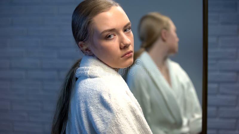Umgekipptes jugendlich Mädchen, das traurig zur Kamera, stehend vor Spiegel, Bedarfshilfe schaut stockfotografie