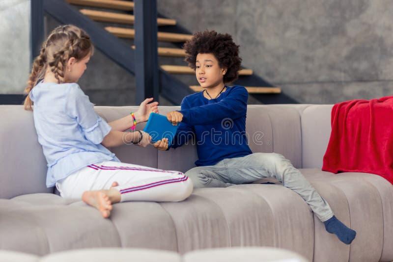 Umgekipptes langhaariges Mädchen, das mit ihrem Mitschüler spricht lizenzfreie stockbilder