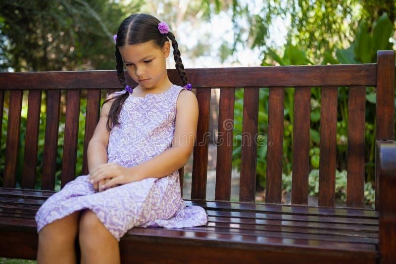 Umgekipptes Mädchen, das unten beim Sitzen auf Holzbank schaut lizenzfreie stockfotografie