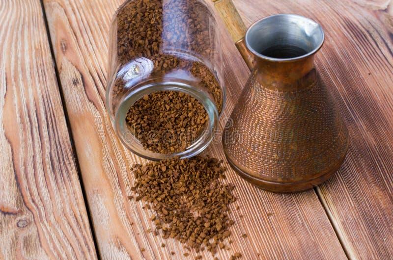 Umgeworfenes cezve mit Kaffeebohnen, Sch?ssel mit gemahlenem Kaffee auf Holztisch lizenzfreie stockfotografie