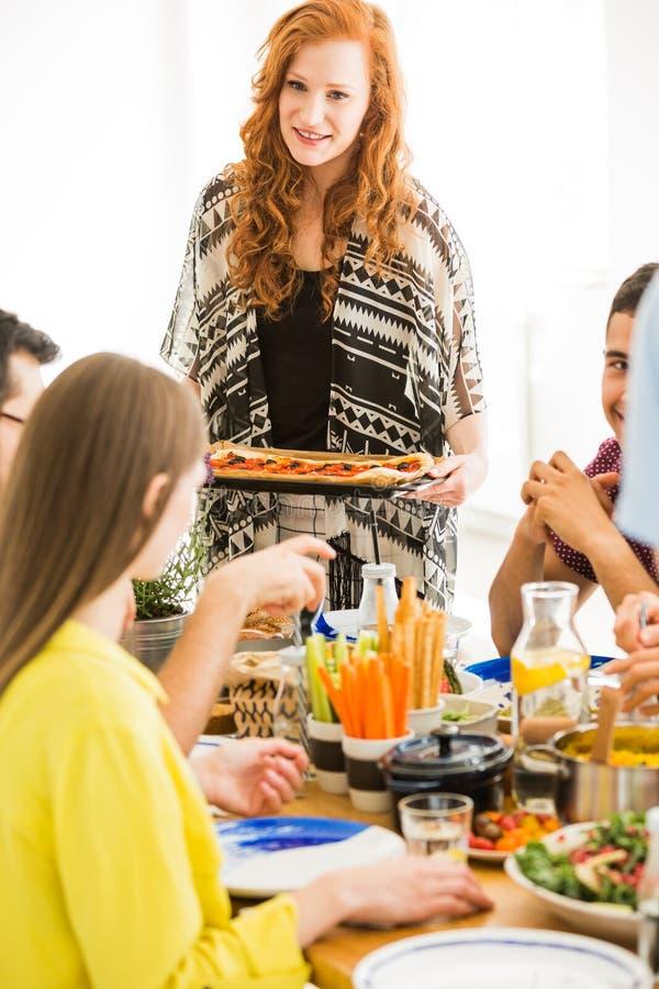 Umhüllungsgemüsepizza der jungen Frau stockbild