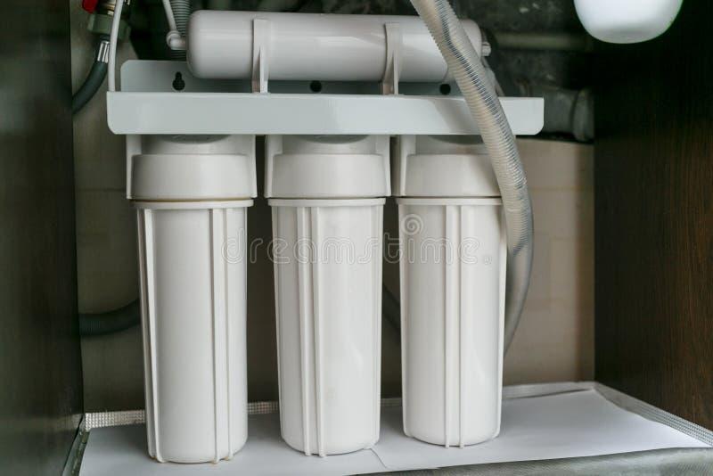 Umkehr-Osmose-Wasseraufbereitungssystem zu Hause Installation von Wasseraufbereitungsfiltern unter Spülbecken im Schrank lizenzfreies stockfoto