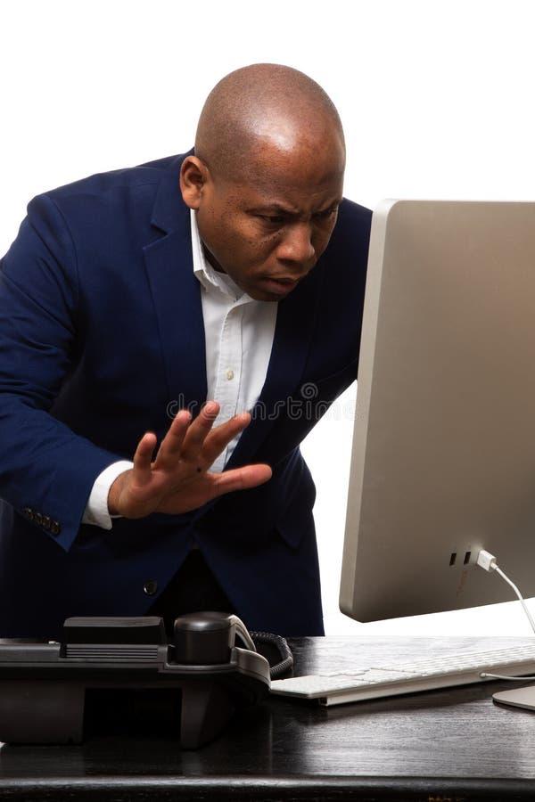 Umkippen-Afroamerikaner-Geschäftsmann Looks At Computer stockfoto