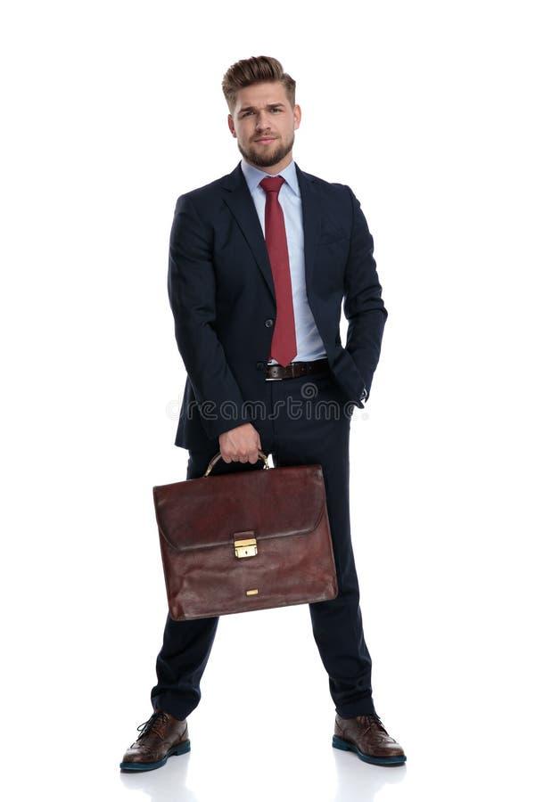 Umkippengeschäftsmann, der seinen Aktenkoffer die Stirn runzelt und hält lizenzfreies stockfoto